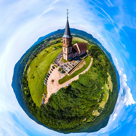Little planet aerial panoramic view of little church in Vosges mountains, Alsace, France. Sunny summer day. Eglise Saint-Gilles de Saint-Pierre-Bois.