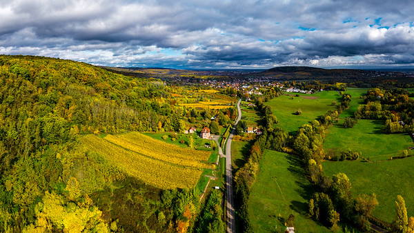 A drone rises above a multi-colored valley in the Vosges.