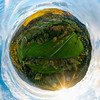 Autumn planet. Sunlit valleys, mountains and a variety of autumn colors. Alsace, France. Little planet projection.