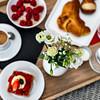 Breakfast in bed. Raspberries, coffee, cake, croissant. Cozy hotel.