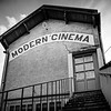 Modern cinema in garage, old building in medieval village, contrast