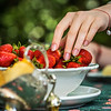 Beautiful female hand with manicure takes a strawberry from a plate. Beautifully laid table. Dessert. Sunlight. Youth and freshness.