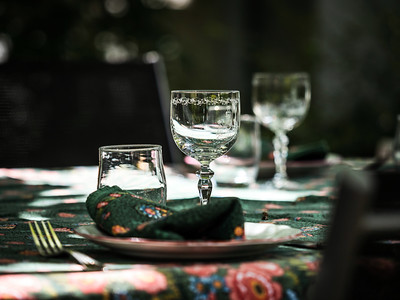 A simple but elegant tablecloth and cutlery laid out on it. Crystal glasses in the sun. Everything is ready for lunch in the garden.