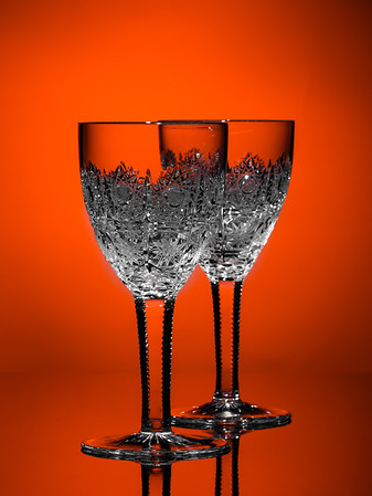 Beautiful crystal wine glass isolated, light reflected in engraved pattern