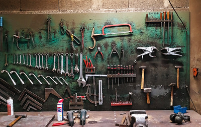 Wall with different metal instruments in little factory room