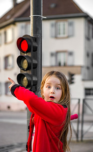 Cute little girl posing with small traffic light