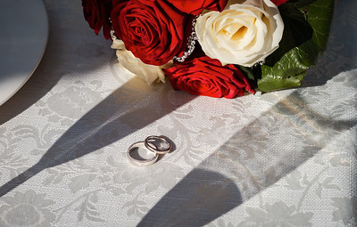 Precious wedding rings and bridal bouquet. Wedding advertising photography.