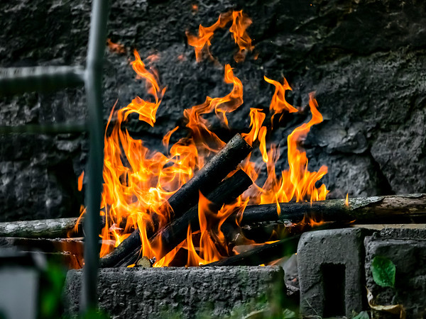Sausages, chicken and meat are grilled on the fire, BBQ in the garden. Beautiful flame.
