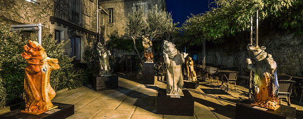 Gothic monster sculptures in summer cafe garden, night view