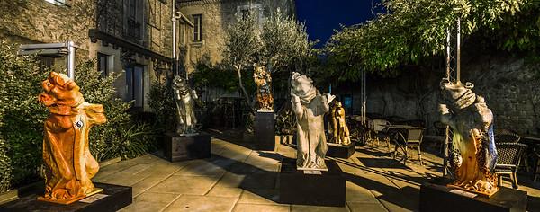 Gothic monster sculptures in summer cafe garden, night view