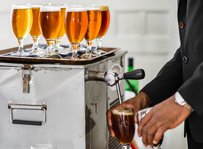 Tapster filling glasses by beer with picon