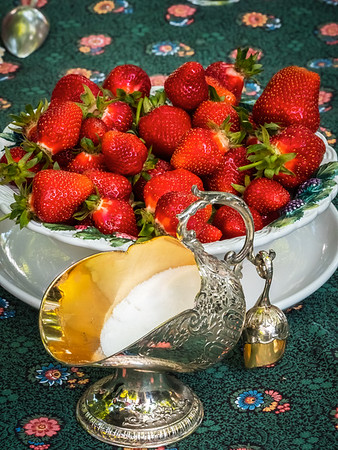 Silver sugar bowl in the shape of a basket for coal. Antique item for the table. Elegant rich dishes for decorating a feast. Strawberries for dessert.