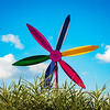 Big abstract metallic flower in public park on blue sky background