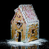 Handmade gingerbread sweet house on black background