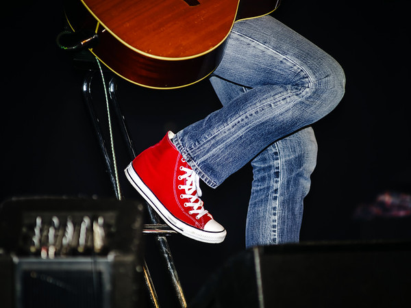Guitarist dressing in jeans and red gumshoes