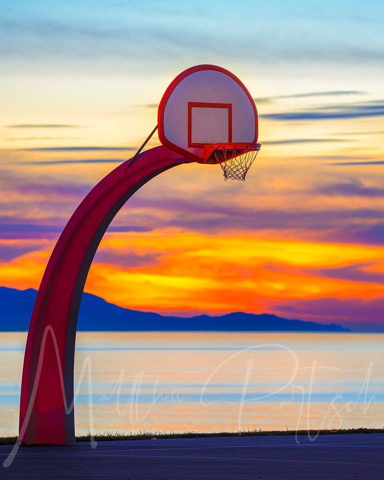 - The Candy Wrapper -<br /> As the sun set with a brilliant color, cars were leaving which enabled their tail lights to light up the basketball hoop.