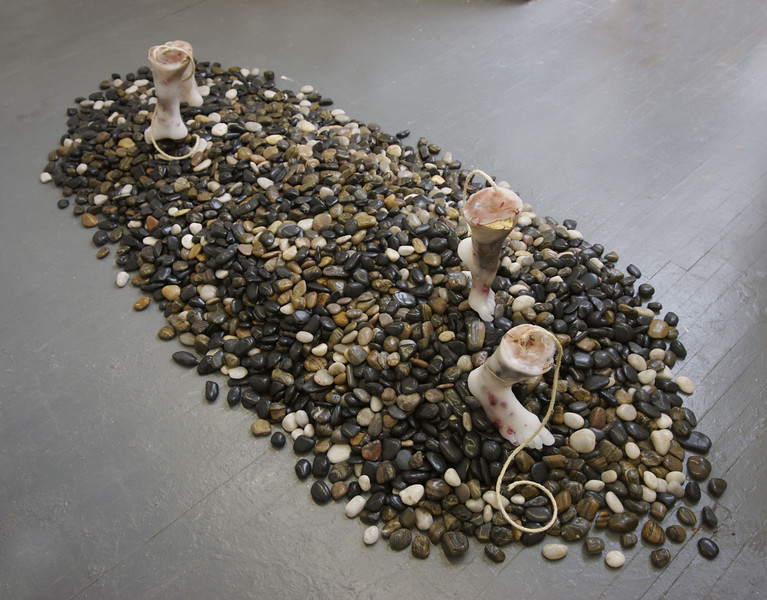 """Severance""<br /> Installation, paraffin wax male & female feet, embedded objects, 350 lbs of river rocks<br /> 8 ft. x 5 ft. x  2ft. high <br /> May 2006"