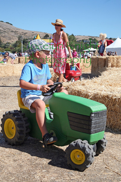 Jasper Nadel, 5, drives a tractor through a haybale maze  followed by his mom, Andrea Nadel, pulling a wagon with 2 year old twins, Addison and Jake at Blackie's Hay Day in Blackie's pasture, Tiburon, Ca on a sunny September 25, 2010.