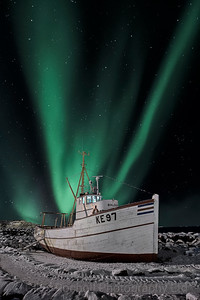 Northern lights over a fishing boat at Keflavik, Iceland.
