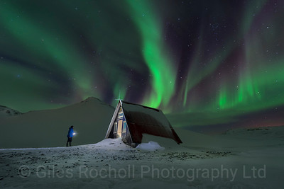 Northern lights illuminate an isolated cabin near Olafsvik, Iceland.
