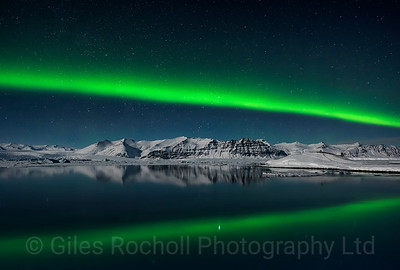The northern lights illuminate the lagoon at Jokulsarlon, Iceland