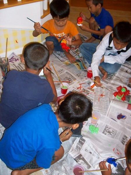 Art Volunteer Carrie Schneider shares plaster painting with the kids in the Burmese Resettlement