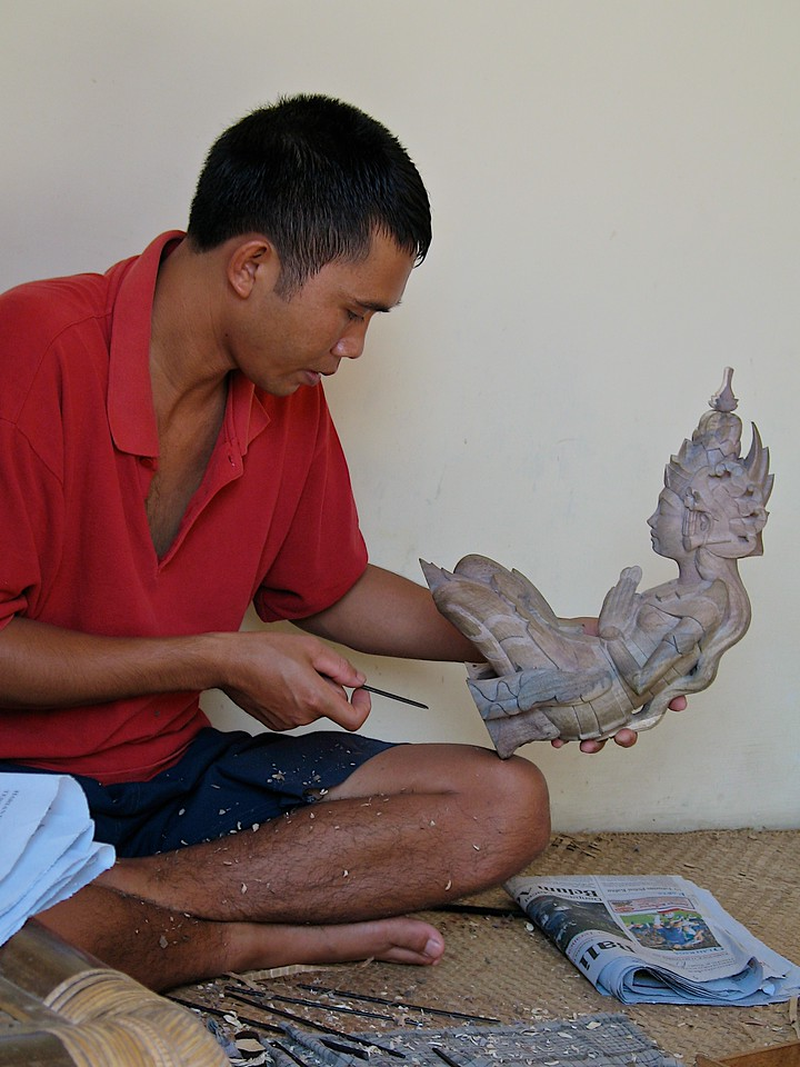 An apprentice carving a mask in Mr Mauka's workshop.