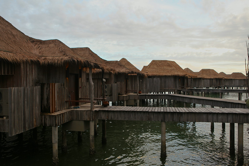 The overwater villas from the island side are reached by walkways.