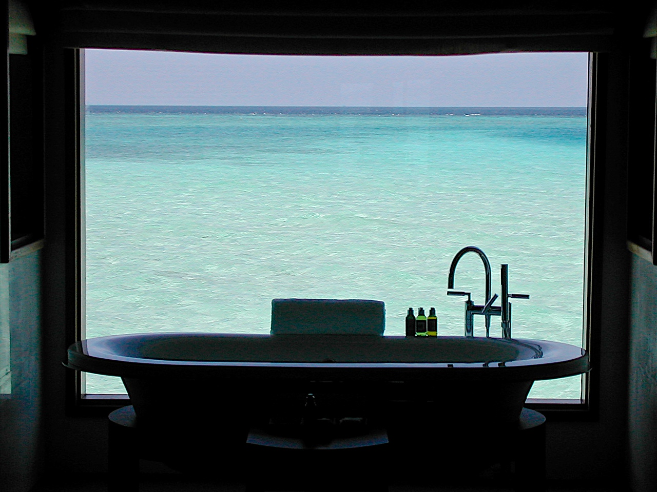 The large soaking tub in the overwater villas have a large window view of the Indian Ocean.