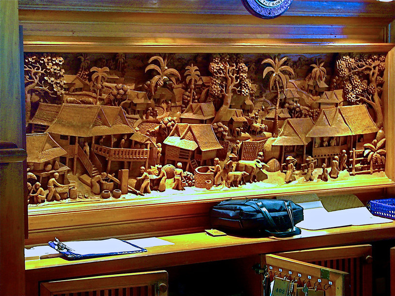 An intricate wood carving behind the reception desk.