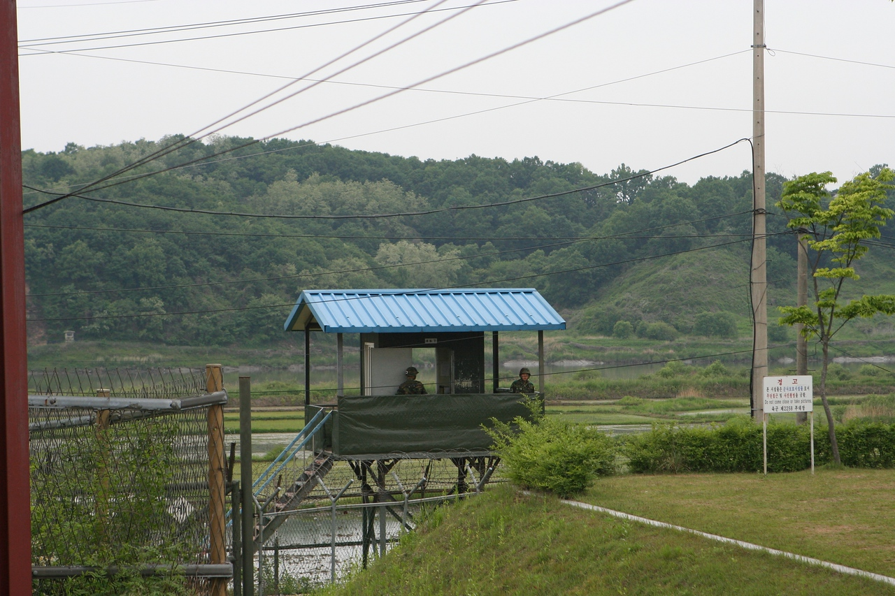 A guard tower behind the razor wire of the Imjin River which flows out of North Korea into the South.  They are not very appreciative of having their pictures taken.