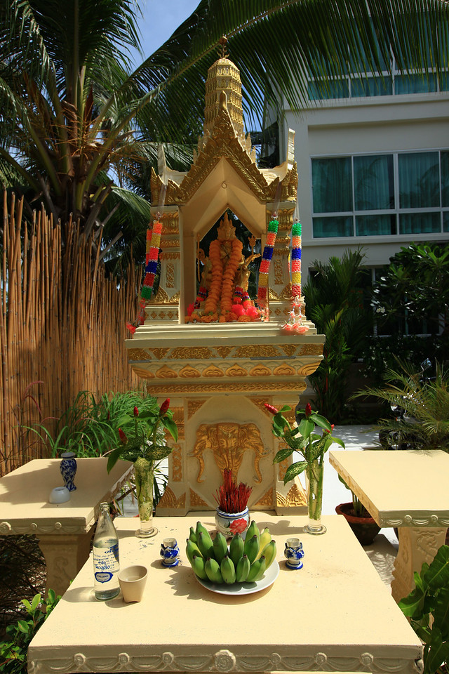 The hotel's spirit house sits right inside the entrance.  A spirit house is a shrine to animist spirits found in the Southeast Asian countries of Cambodia, Laos, and Thailand. Most houses and businesses have a spirit house placed in an auspicious spot, most often in a corner of the property. The location is often chosen after consultation with a Brahmin priest. The spirit house is normally in the form of a miniature temple and is mounted on a pillar or on a dais.<br /> The house is intended to provide a shelter for spirits which could cause problems for the people if not appeased. Offerings are left at the house to propitiate the spirits.