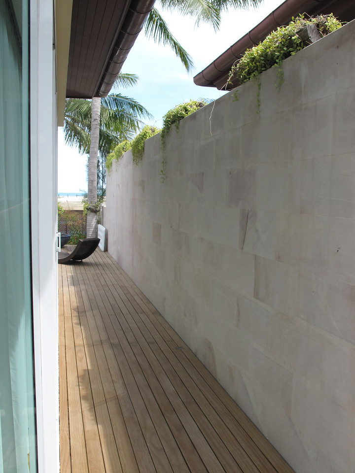 A narrow walkway leads down to two buildings, one with two bedrooms and the other with a living room and kitchen.  Beyond those are the pool and the beach.