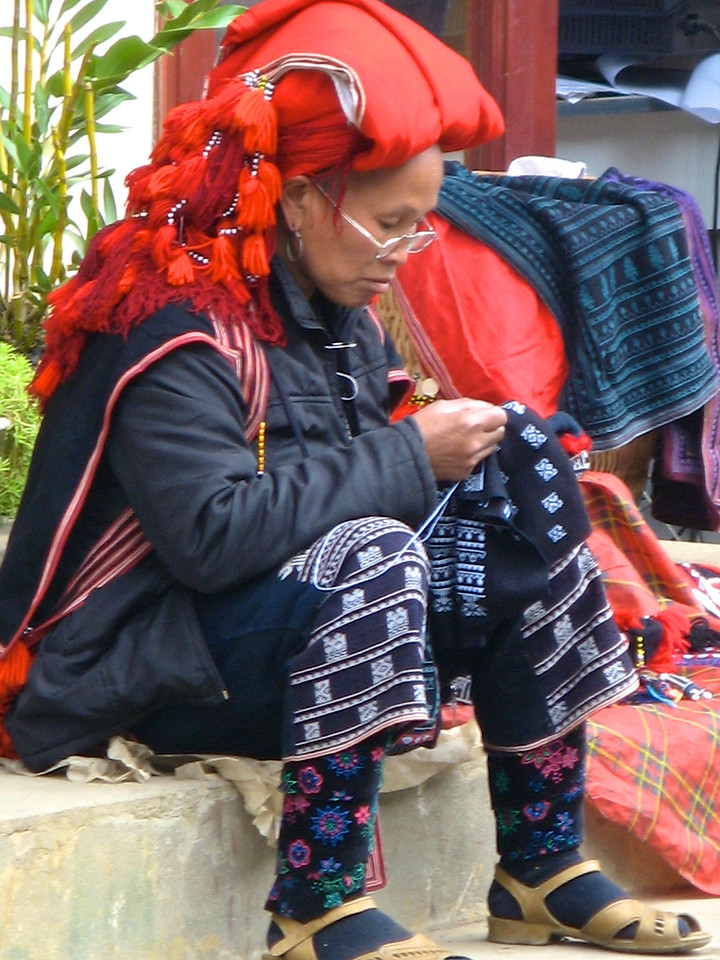 Here a Red Hmong does some embroidery along the side of the street.