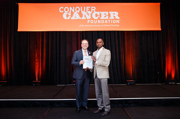 V.K Gadi, MD, PhD of University of Washington accepting the Young Investigator Award on behalf of Sarah Buckley, MD with Thomas G. Roberts, Jr., MD, Chair of the Conquer Cancer Foundation Board of Directors, during 2017 Grants & Awards Ceremony and Reception