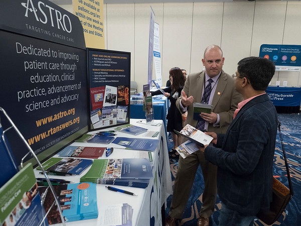 Exhibitor in front of booth speaking with attendee during Exhibit Hall
