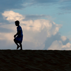 Boy walking on sand dune at Mingsha Shan, Dunhuang, Jiuquan, Gansu Province, China