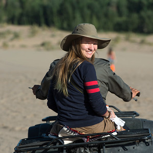 Woman enjoying quadbike ride in desert at Mingsha Shan, Dunhuang, Jiuquan, Gansu Province, China