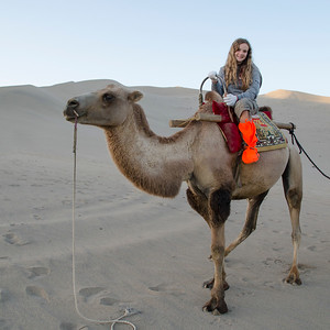 Girl riding camel at Mingsha Shan, Dunhuang, Jiuquan, Gansu Province, China