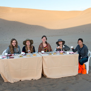 Family enjoying breakfast in desert at Mingsha Shan, Dunhuang, Jiuquan, Gansu Province, China