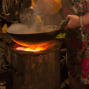 Woman's hand cooking food in wok.