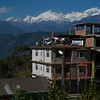Buildings in village with snow covered mountains in the background, Kaluk, Sikkim, India