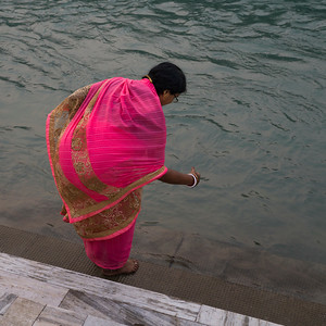 Woman performing devotional ritual on the River Ganges during Ganga Aarti, Rishikesh, Dehradun District, Uttarakhand, India
