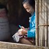 Senior woman cutting food with knife, Ban Gnoyhai, Luang Prabang, Laos