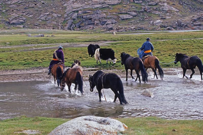 Horsemen crossing river. Blue Lake mongolia