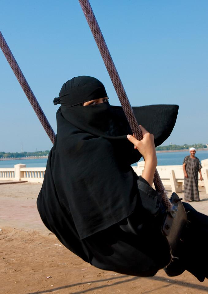 Saudi Arabia, Mecca Region, Jeddah, Girl In Abaya On A Swing