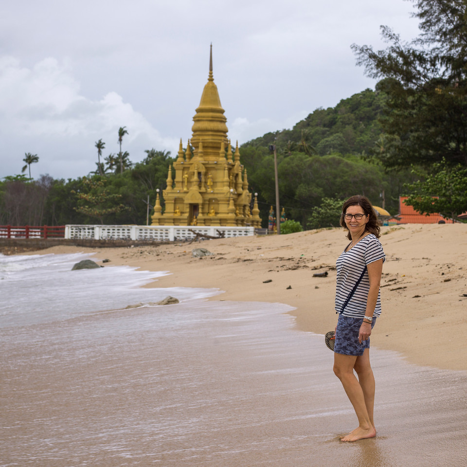 Female tourist standing on beach with Laem Sor Pagoda in the background, Koh Samui, Surat Thani Province, Thailand