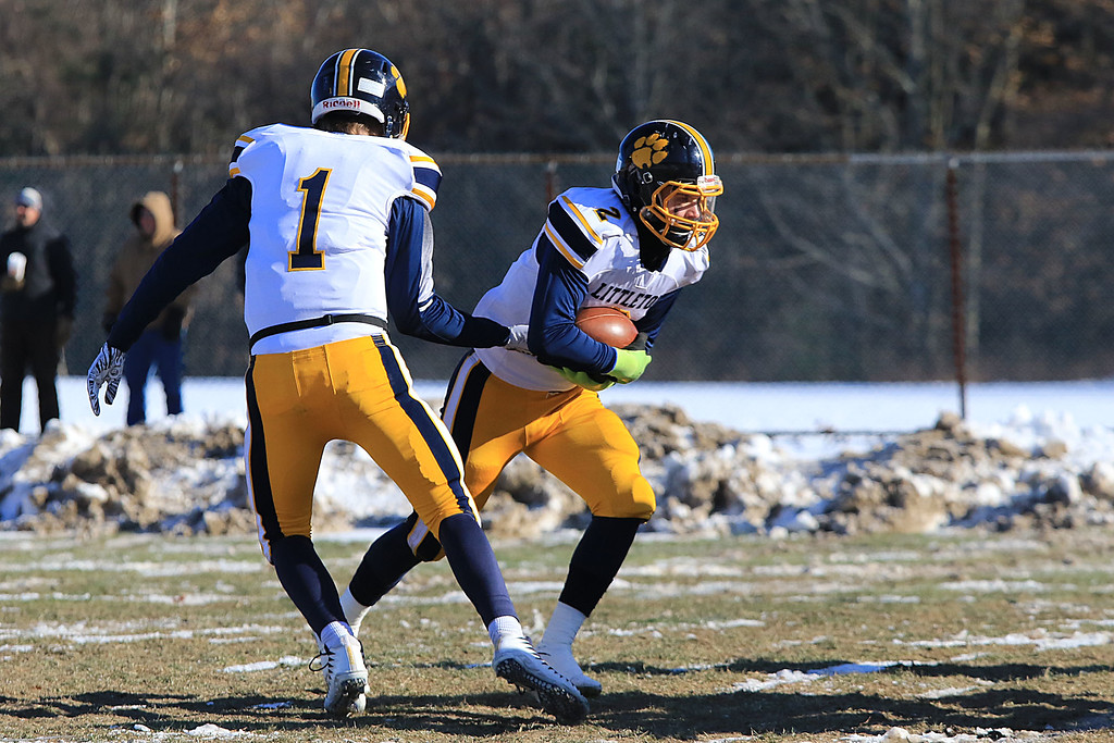 . Littleton High School visited Ayer Shirley Regional High School on Thanksgiving Day for there annual turkey day game. LHS quarterback Braden Lynn hands off the ball too running back Will Scott. SENTINEL & ENTERPRISE/JOHN LOVE