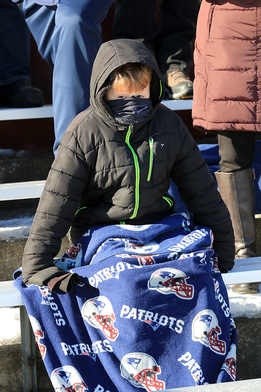 . Littleton High School visited Ayer Shirley Regional High School on Thanksgiving Day for there annual turkey day game. Ayer fan Cole Brussard, 11, tries to stay warm as he watches the game. SENTINEL & ENTERPRISE/JOHN LOVE