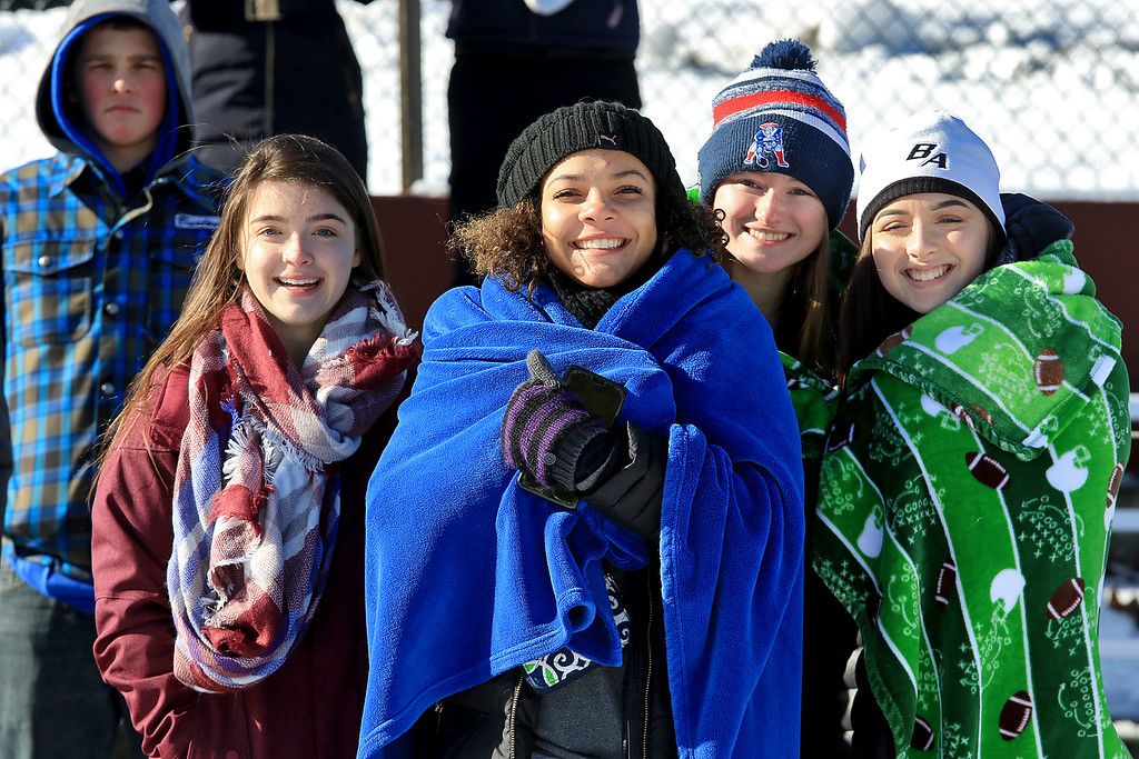 . Littleton High School visited Ayer Shirley Regional High School on Thanksgiving Day for there annual turkey day game. ASRHS fans senior Rachel Arsenault, sophomore Julianna aNealy, juniors Mackenzie Marshall and Riley Murphy try and stay warm as they watch the game. SENTINEL & ENTERPRISE/JOHN LOVE